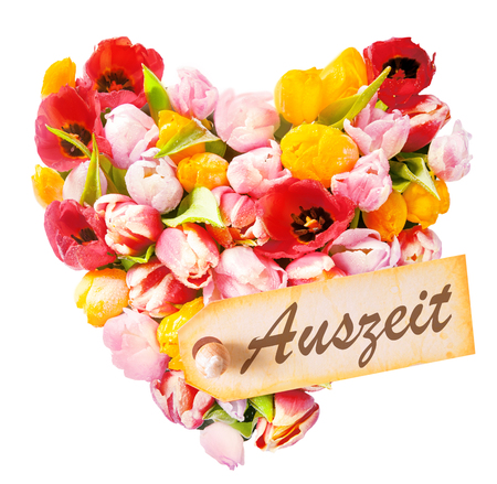 auszeit: Relaxing heart-shaped greeting with an arrangement of beautiful mulitcoloured fresh tulips isolated on white with a gift tag reading - Best Mom - german called Auszeit Stock Photo