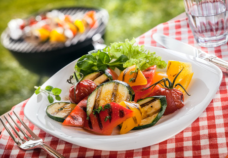 Serving of succulent roasted vegetarian, fresh vegetables with sweet peppers, marrow, tomato and herbs on a garden table at a BBQ with a red and white checked tablecloth.