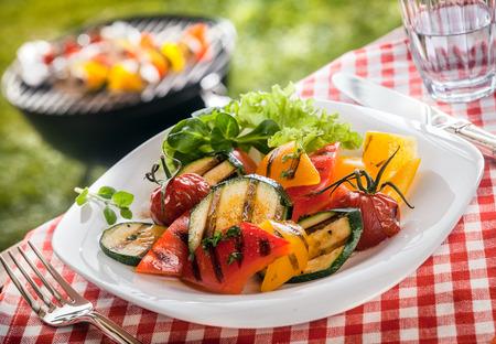 accompagnement: Servir de succulentes grill�es v�g�tariens, l�gumes frais avec les poivrons, les tomates, la moelle et des herbes sur une table de jardin avec barbecue avec un carreaux rouges et blancs nappe.