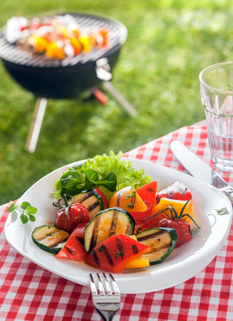 Plates: Delicious healthy plate of colorful roasted vegetables with marrow, tomato , sweet peppers and herbs garnished with frilly lettuce on a picnic table in a summer garden with a barbecue behind