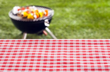 parrillada: Fondo vacío mesa de picnic cubierta en un fresco del campo de color rojo y blanco comprobado tela para su colocación de productos o publicidad con una barbacoa en un césped verde detrás Foto de archivo