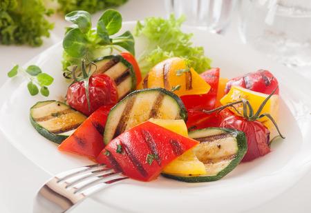 채식의 맛있는 구운 된 diced 신선한 야채 신선한 허브와 화려한 달콤한 피망, 토마토 및 아기 골 수의 혼합물과 함께 filly 양상추와 garnished 하얀 그릇에