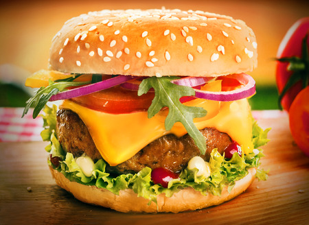Homemade cheeseburger or burger on a sesame bun with a succulent ground beef patty, melting cheddar cheese, onion, rocket, tomato and lettuce, close up with vignetting photo