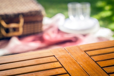 placement: Empty slatted wooden picnic table for your product placement with a blurred wicker picnic hamper and rug with glasses and plates on a green lawn behind