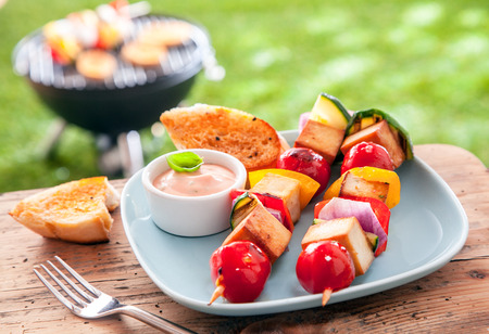 bbq picnic: Healthy summer meal of halloumi and vegetable kebabs roasted over an outdoor barbeque in the garden and served with a savory sauce and toasted baguette on a picnic table