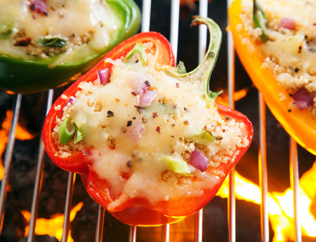 coals: Savory stuffed sweet bell pepper with melted cheese grilling over the hot glowing coals on an outdoor barbecue, close up overhead view