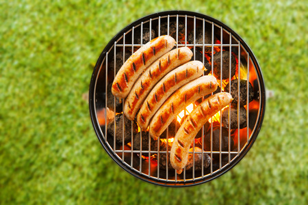 barbecue fire: View from above on a green grass background of a row of pork and beef bratwurst grilling over a barbecue fire on a hot day during the summer vacation Stock Photo