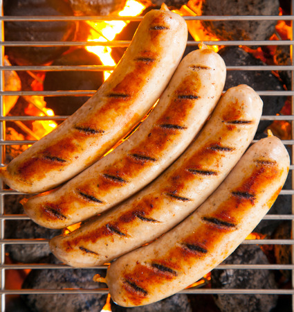 coals: Delicious sausages called bratwurst, on a metal grid grilling over hot coals on a BBQ for a picnic lunch on a summer vacation