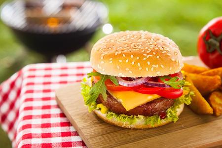 Smakelijke cheeseburger met gesmolten cheddarkaas druipt over de grond rundvlees hamburger gegarneerd met verse ingrediënten voor de salade en geserveerd op een houten tafel op een outdoor picknick tafel