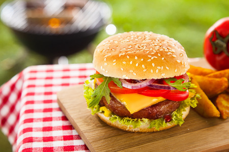 on the tablecloth: Tasty cheeseburger with melted cheddar cheese dripping over ground beef burger garnished with fresh salad ingredients and served on a wooden table on an outdoor picnic table Stock Photo