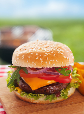 Delicious homemade cheeseburger on a summer picnic table outdoors with a succulent ground beef patty topped with melted cheese and garnished with fresh salad ingredients on a sesame bun Stock Photo