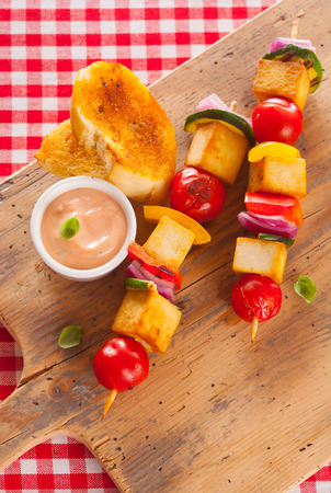 Wholesome country halloumi and vegetable kebabs served on a wooden board on a picnic table covered with a fresh red and white checkered cloth, overhead view photo