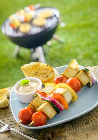 Outdoors Summer bbq smoked tofu on a table with a tofu kebab and a grill in the background photo