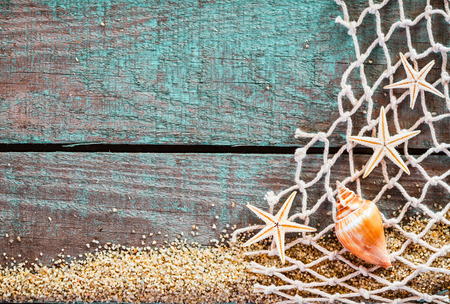Rustic marine background with copyspace on weathered turquoise blue wooden boards decorated with diamond mesh fish net, starfish and a seashell on a bed of beach sand