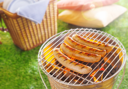 hamper: Cooking the meat at a summer bbq, bratwurst, with a row of delicious seared sausages grilling over the hot coals alongside a wicker picnic hamper on green grass
