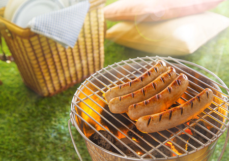 coals: Sausages grilling or glowing hot coals in a portable metal barbecue on a summer picnic with a wicker hamper with plates and cushions on the green lawn alongside Stock Photo