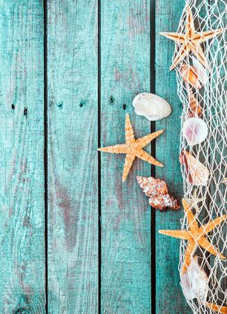 Marine grens van visnet met schelpen en zeesterren op rustieke turquoise blauwe houten planken met een verweerde woodgrain textuur en copyspace