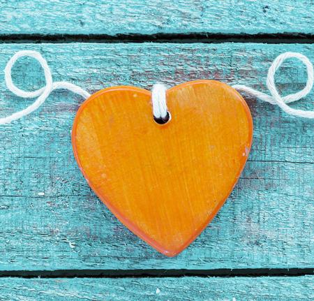 バレンタインや記念日の装飾的なコイル状ロープのロマンチックなカラフルなテクスチャ ターコイズ ブルー木製の背景にオレンジ木製中心部 写真素材