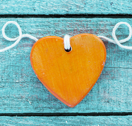 Romantic orange wooden heart on a colourful textured turquoise wood background with decoratively coiled rope for Valentines or an anniversary photo