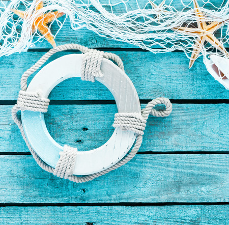 Maritime decoration in a themed background with copyspace on turquoise blue wooden planks decorated with a life ring, starfish and fishing net in square format photo