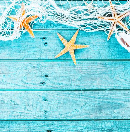 estrella de mar: Bastante azul turquesa fondo náutica decorado con red de pesca drapeado y estrellas de mar sobre tablas de madera rústicos pintados con copyspace adecuadas como un formato cuadrado tarjeta o invitación del partido,