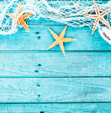 Pretty turquoise blue nautical background decorated with draped fishing net and starfish on painted rustic wooden boards with copyspace suitable as a card or party invitation, square format photo