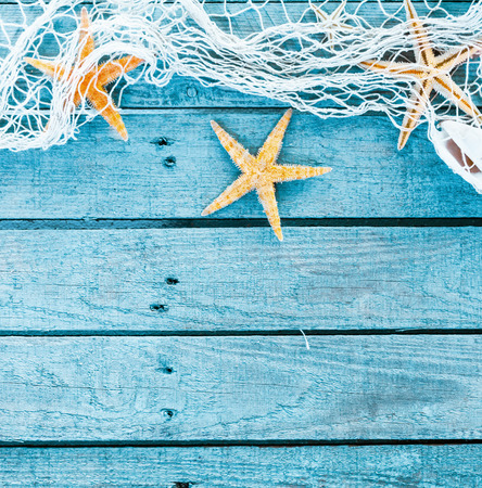 themed: Sea themed turquoise blue square background of blue painted rustic wooden boards decorated with a border of draped fishing net and starfish with copyspace for your text or advertising