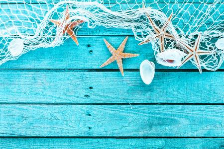 繊細な航海国境漁網で、貝殻およびヒトデ カラフルな青緑色の背景に青のテキストの copyspace と塗られた木の板