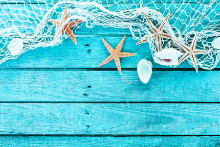 the ocean: Delicate nautical border with fishing net, sea shells and starfish on a background of colourful turquoise blue painted wooden boards with copyspace for your text