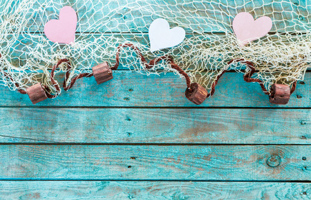 Pretty pink and white hearts in a fishing net border with corks symbolising love and romance on turquoise blue wooden boards for your Valentines,anniversary or wedding greeting, horizontal format photo