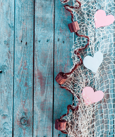 Border of romantic pink and white hearts in fishing net with an edge decoration of corks in vertical format on rustic turquoise blue boards with copyspace for your Valentine or anniversary greeting photo