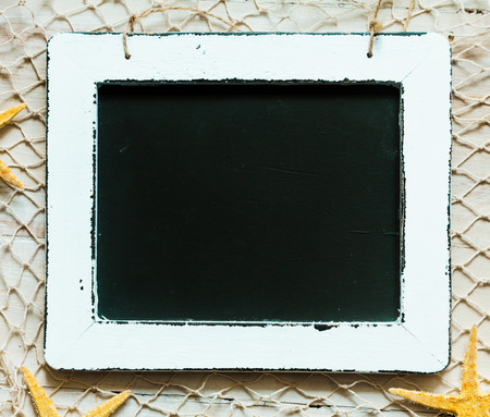 blank slate: Blank black vintage school slate surrounded by a worn white wooden frame and fishing net with scattered orange starfish in a nautical theme with copyspace Stock Photo