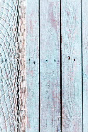 Fishing net former a vertical border on the left of old rustic blue painted weathered wooden boards with copyspace in a marine background Stock Photo