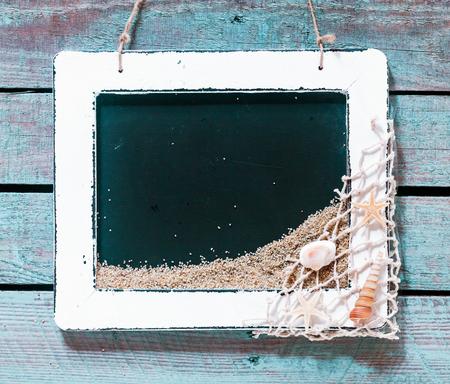 enclosing: Vintage bianco cornice in legno che racchiude una lavagna nera vuota con copyspace decorato in un angolo con rete da pesca e conchiglie su tavole di legno rustico, in formato quadrato