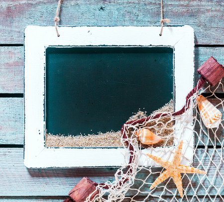 blank slate: Vintage blank black school slate in an old worn white wood frame with copyspace and a marine decoration of shells and starfish arranged on fishing net in one corner on a rustic old wooden boards
