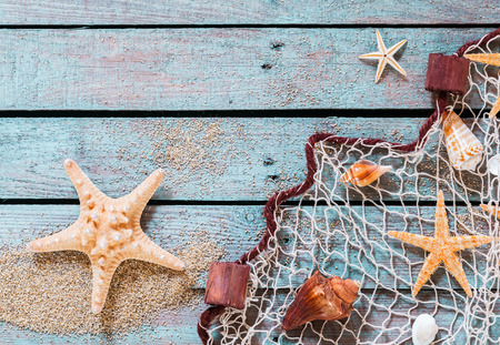 Marine still life on rustic wooden boards with scattered golden beach sand with a spiny starfish and fishing net covered in carefully arranged shells and sea stars with copyspace photo