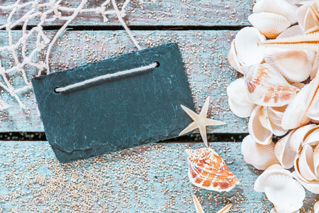 blank slate: Old slate with a seashell collection, fishing net and a starfish on a rustic wooden background covered with scattered golden beach sand with copyspace
