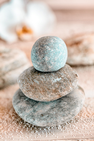 spirituality therapy: Carefully balanced and stacked naturally rounded water worn Zen stones at a marine spa conceptual of spirituality, therapy, wellness, relaxation and meditation Stock Photo