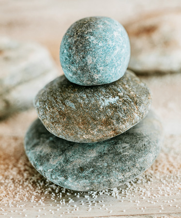 Spirituality and enlightenment with a balanced stack of smooth waterworn Zen stones at a spa depicting tranquility, wellness, relaxation and rejuvenation photo