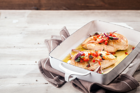 Serving of golden roasted chicken breasts in a metal oven dish topped with diced red pepper,onion and herbs and served on a picnic table with copyspace photo