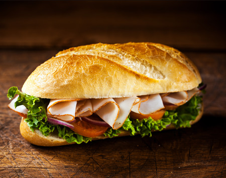 Fresh crusty golden roll with sliced ham and salad ingredients including lettuce, tomato and onion standing ready prepared for a tasty snack on a wooden table with copyspace photo