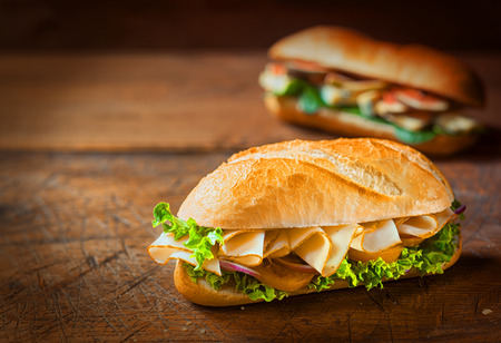 vignetting: Delicious golden crusty ham roll with onion, lettuce and tomato on a rustic wooden table with vignetting and copyspace Stock Photo