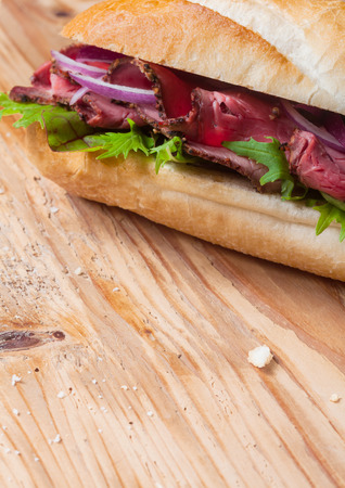 Fresh baguette with a filling of sliced roast beef, lettuce, tomato, onion and herbs on a wooden table top with a pretty woodgrain pattern and copyspace photo