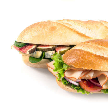 Two fresh crusty baguettes with savory filling, one with sliced figs, spinach and blue cheese and the other with processed sliced chicken and salad on white in square format photo