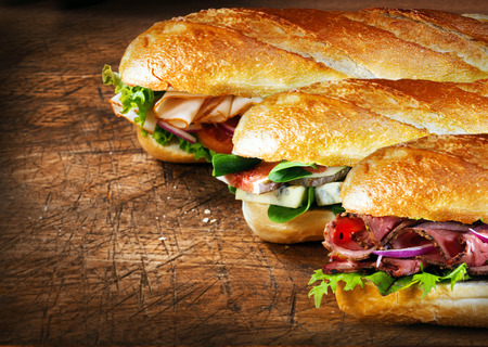 baguette: Three tasty baguettes with savory fillings lined up on a rustic wooden countertop with roast beef and rocket, figs and cheese, and chicken and salad fillings