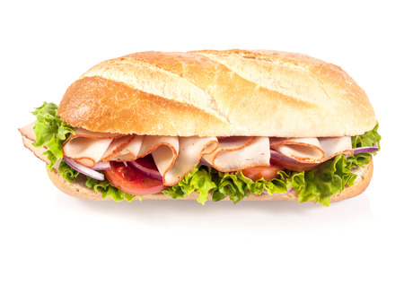Crusty golden French baguette with sliced chicken, tomato and frilly lettuce, high angle view on a white background photo