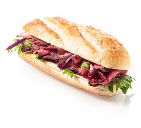 french roll: Healthy lean roast beef with leaves of fresh rocket on a freshly baked crusty roll or baguette viewed at an angle on a white background