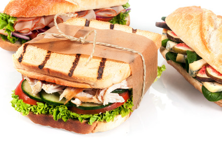 Choice of delicious fresh lunchtime sandwiches served on crusty baguette or grilled toast with chicken and salad or blue cheese and fig fillings, closeup on a white background photo