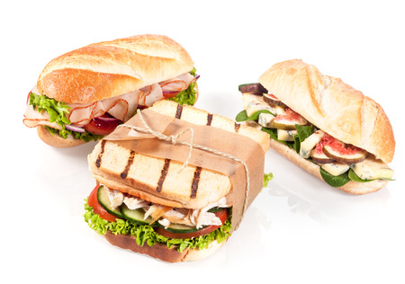 Three gourmet sandwiches with chicken breast and salad on grilled toast or chicken slices with lettuce, and blue cheese with figs on crusty baguette, on white photo