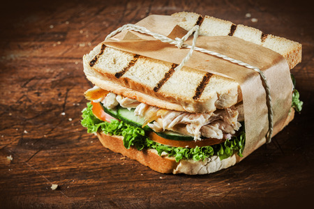 Toasted shredded chicken breast and salad sandwich served on a rustic wooden table wrapped in a brown paper wrapper tied with string with vignetting and copyspace photo